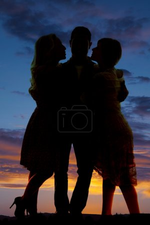 silhouette man between two women sunset