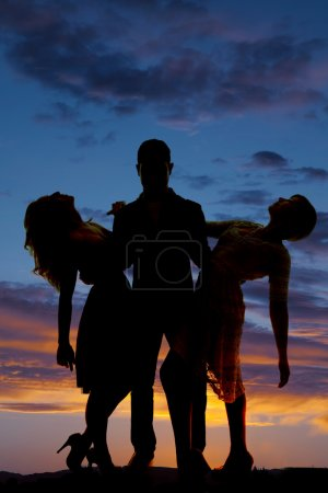 silhouette man hold two women leaning back sunset