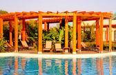 Plavecký bazén, dřevěné pergoly a lehátka