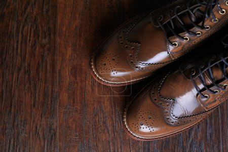Photo for A pair of luxury brown shoes close up on wood background. - Royalty Free Image