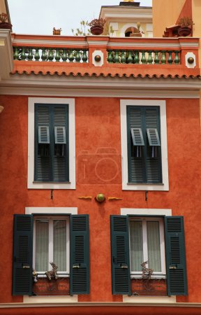 Red stucco house with old green shutter windows in Monaco