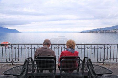 Senior man and woman relaxing at lake Geneva, Switzerland