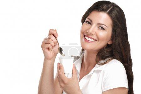 young beautiful smiling woman eating fresh yogurt