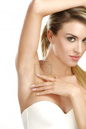 Photo for Beautiful woman showing her perfectly shaved armpit on white - Royalty Free Image