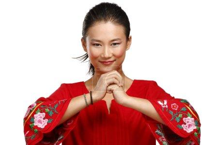 Photo pour Femme chinoise, saluant le geste en élégante robe rouge sur blanc - image libre de droit
