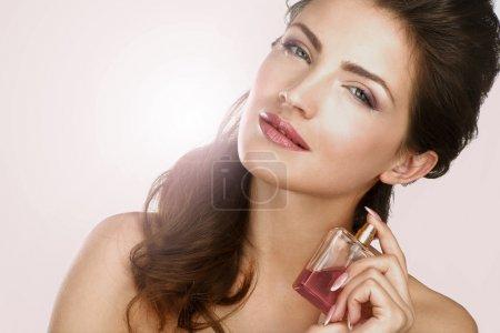 Photo pour Gros plan d'une belle femme en appliquant l'effet de contre-jour de parfum - image libre de droit