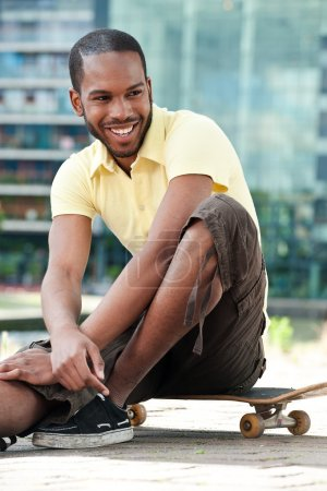 Photo for A young black male sitting on a skateboard and relaxing - Royalty Free Image
