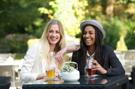 Photo for Two girls drinking tea and laughing at a cafe - Royalty Free Image