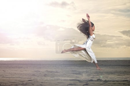 Photo for An african girl jumping in a white dress at the beach - Royalty Free Image