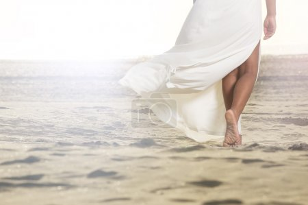 Photo for An African American girl is walking on the sand with a flowing white dress. - Royalty Free Image
