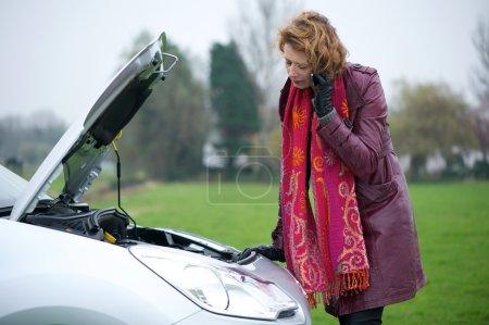 Photo pour Femme caucasienne appelant à l'assistance routière sur son téléphone portable. la hotte est sur sa voiture et il y a panne de moteur. - image libre de droit