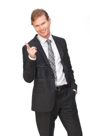 Photo pour Bel homme d'affaires, vêtu d'un costume et une cravate pointe son doigt vers vous. Il a un sourire sur son visage et la main dans sa poche. isolé sur fond blanc - image libre de droit