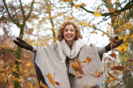 Photo for Middle aged woman throwing leaves in autumn with open arms - Royalty Free Image