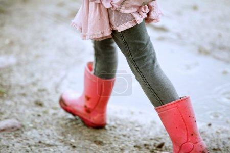 Photo pour Fermer la petite fille marchant à l'extérieur avec des bottes rouges - image libre de droit