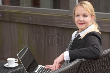 Business woman relaxing with laptop and cup of coffee outdoors
