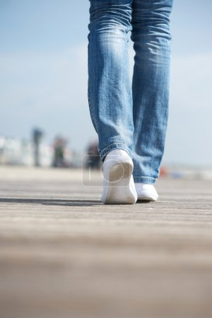 Portrait of a woman walking in blue jeans and comfortable white shoes