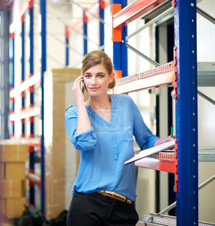 Businesswoman talking on mobile phone in warehouse