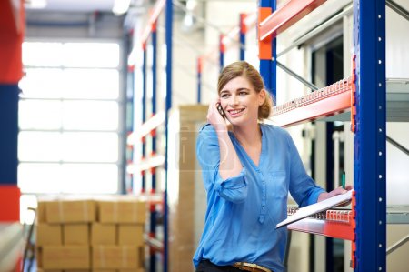 Female logistics worker controlling stock and talking on cellphone in warehouse