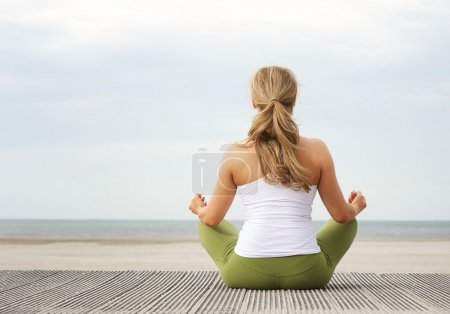 Rear view portrait of young woman sitting at beach in yoga pose