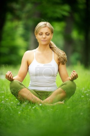 Beautiful young woman sitting in yoga pose in the park