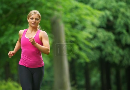 Beautiful young woman running in the park in sportswear