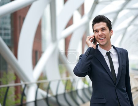 Smiling business man talking on mobile phone in the city