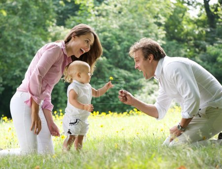 Happy family with child giving flower to father