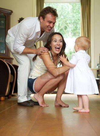 Photo pour Portrait d'un couple de parents heureux aidant bébé à faire les premiers pas - image libre de droit