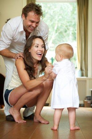 Photo pour Portrait d'une famille heureuse souriant comme bébé fait ses premiers pas - image libre de droit