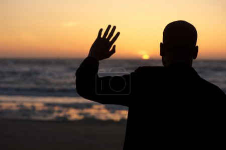 Male silhouette waving at sunset at the beach