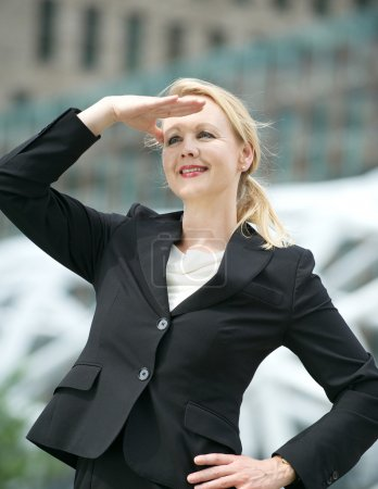 Business woman standing with hand salute outdoors