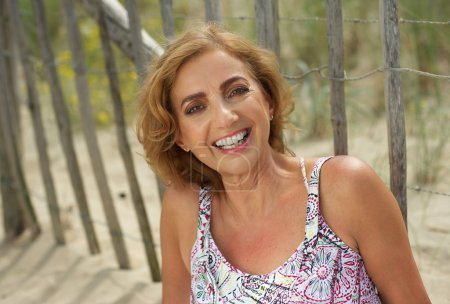 Attractive middle aged woman smiling outdoors
