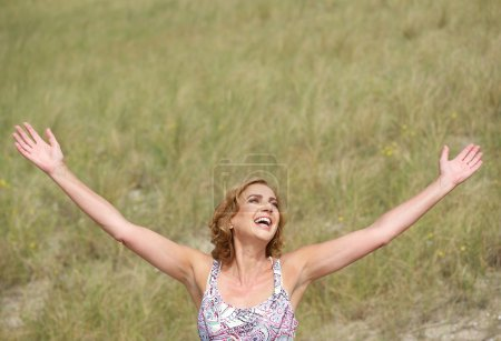 Photo for Portrait of a carefree woman standing with arms outstretched - Royalty Free Image