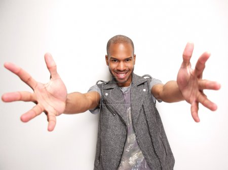 Smiling man with arms outstretched and hands open
