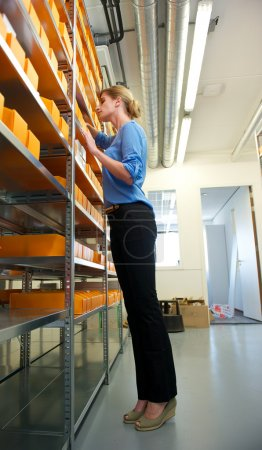 Female employee searching through boxes on shelves