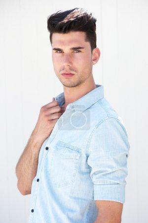 Photo pour Portrait rapproché d'un beau mannequin masculin debout sur fond blanc - image libre de droit