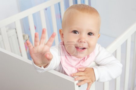 Portrait of a cute baby waving hello and smiling from crib