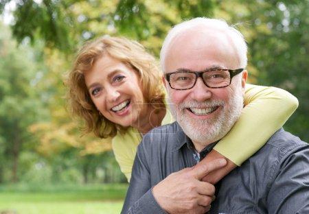 Happy older woman embracing smiling older man