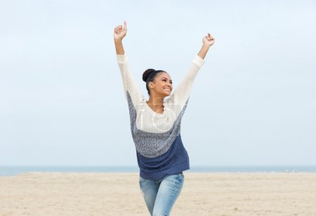 Photo for Closeup portrait of a carefree young woman with arms outstretched walking on the beach - Royalty Free Image