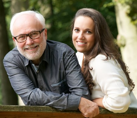 Mature father and young daughter smiling outdoors