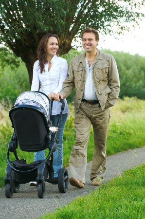Mother and father walking outdoors with baby stroller
