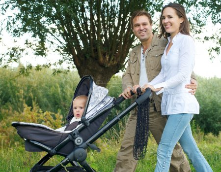 Father and mother smiling outdoors and walking baby in pram