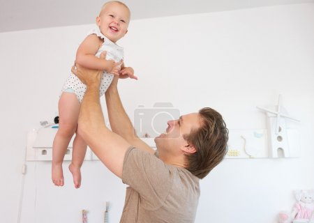 Happy father playing with cute baby at home