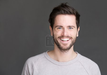 Photo for Closeup portrait of a happy young man smiling on gray background - Royalty Free Image