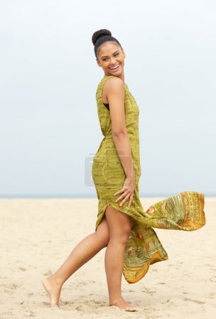 Portrait of a cheerful young woman walking at the beach