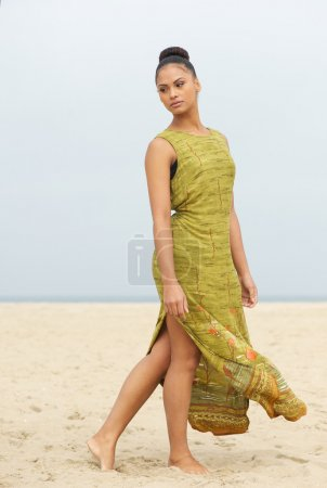Portrait of an elegant fashion model walking at the beach