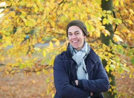 Portrait of a happy young man smiling outdoors in warm clothing