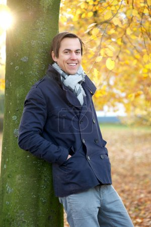 Relaxed man smiling outdoors on an Autumn day