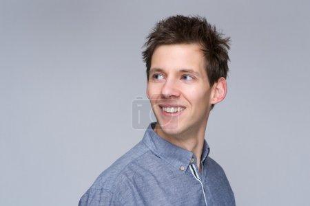 Photo pour Gros plan le portrait d'un homme souriant cherche loin sur fond gris - image libre de droit