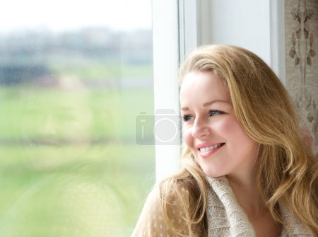 Woman looking outside through window